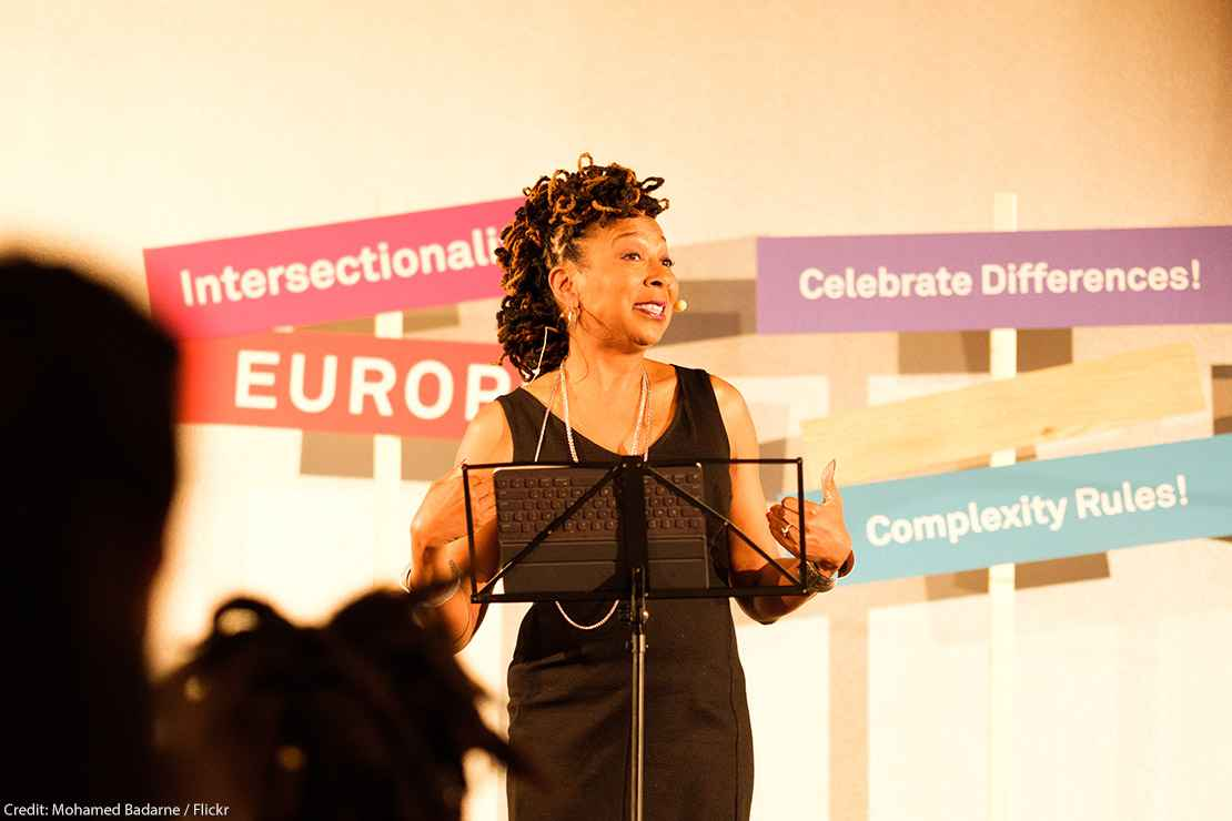 """Kimberlé Crenshaw gives presentation at podium with """"Intersectionality"""" and """"celebrate differences"""" sign behind her."""