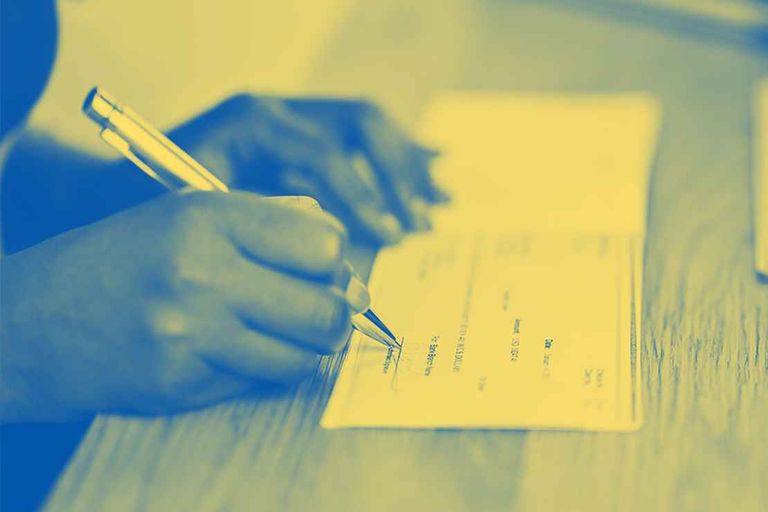 A yellow tinted image on someone signing a check on a desk.