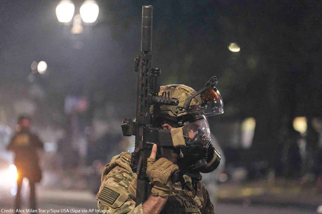 An ICE agent holds his weapon in the air as federal officers clear Main Street in Portland, Ore., on July 26, 2020.